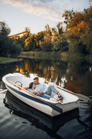 Love couple lying in a boat on lake at sunset Stock Photo