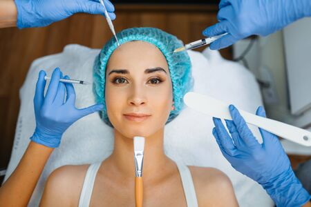 Cosmetician hands with working tools, patient face