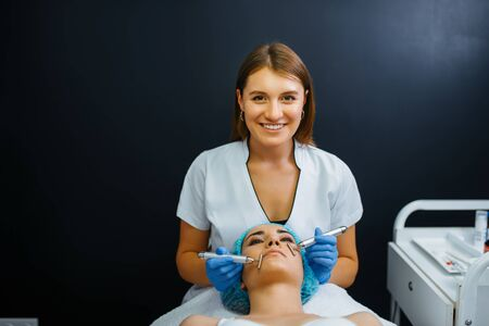 Cosmetician smoothes face after botox injections