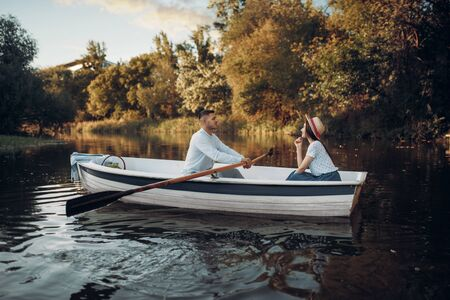 Love couple boating on lake, water reflection