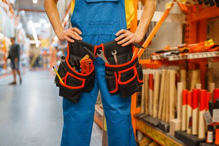 Male builder trying on tool belt in hardware store