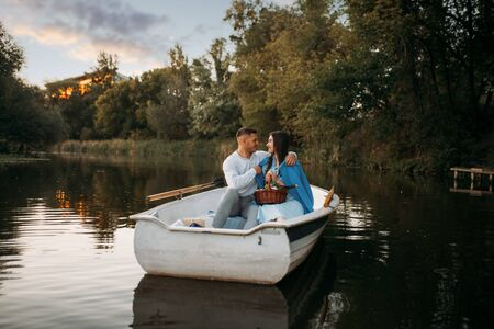 Love couple hugs in a boat on quiet lake at sunset Reklamní fotografie - 133066896