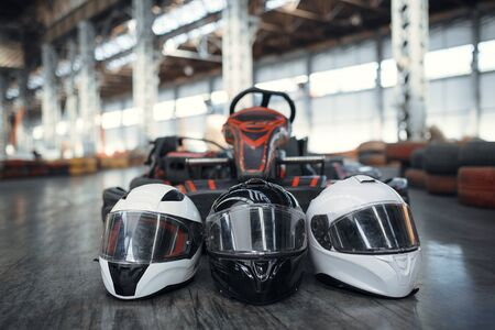 Go kart car and helmets on the ground, karting auto sport indoor. Speed racing go-kart track. Fast vehicle competition, hot pursuit