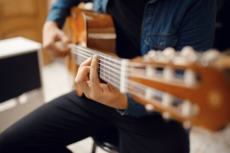 Male guitarist trying to play on acoustic guitar in music store. Assortment in musical instruments shop, musician buying equipment