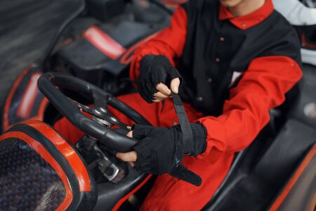 Kart racer in red uniform puts on gloves