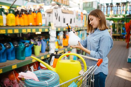 Female customer choosing tools, shop for gardeners Imagens