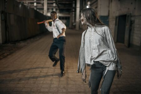 Man with axe attacked female zombie 写真素材