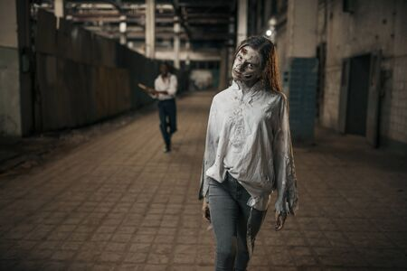 Man with axe catching up female zombie