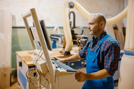 Carpenter at pc works with woodworking machine