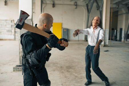 Military man with axe, zombie in abandoned factory 版權商用圖片