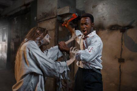Man with pipe wrench kills female zombie, horror 版權商用圖片