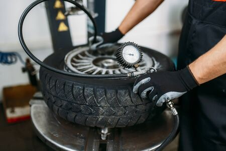 Mechanic inflates wheel, tire repairing service