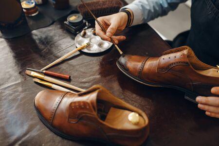 Bootmaker with brush tints shoes, footwear repair service. Craftsman skill, shoemaking workshop, cobbler shop Stock Photo