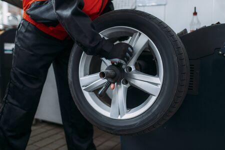Repairman puts the wheel on the balancing machine
