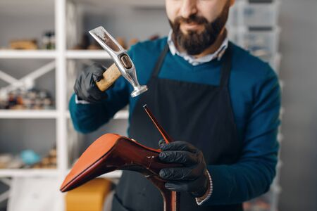 Shoemaker with hammer nails tips to the shoe