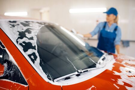 Female washer with sponge wipes the automobile windshield, car wash. Woman cleans vehicle, a carwash shop