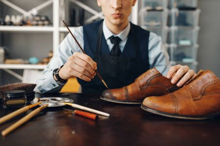 Bootmaker with brush tints shoes, footwear repair service. Craftsman skill, shoemaking workshop, master works with boots, cobbler shop
