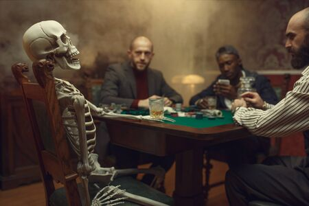 Poker players and skeleton at gaming table, fun 写真素材 - 136087910