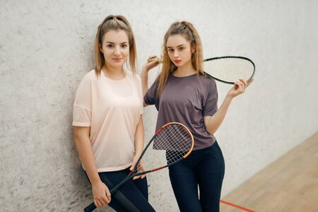 Two female players poses with squash rackets