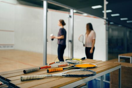 Squash rackets on the table, players on background