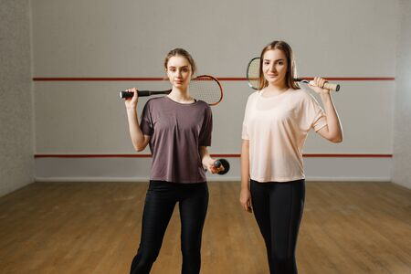 Two female players shows squash rackets