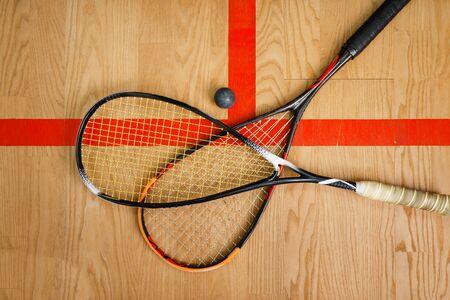 Dos raquetas de squash y pelota en el piso de la cancha, vista superior, nadie, concepto de juego. Pasatiempo deportivo activo, entrenamiento físico para un estilo de vida saludable
