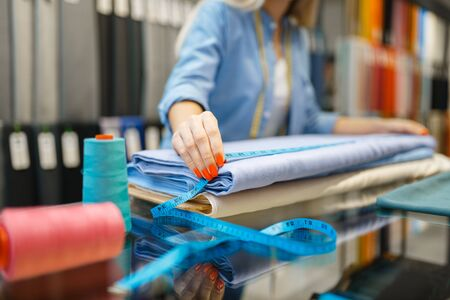 Female seller measures fabric in textile store. Shelf with cloth for sewing on background, clothing patterns choice in shop