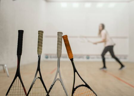Squash rackets, female player on background