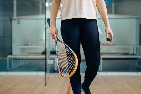 Female person shows squash racket and ball Imagens