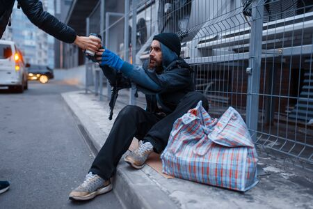 Male person gives cup of hot coffee to homeless