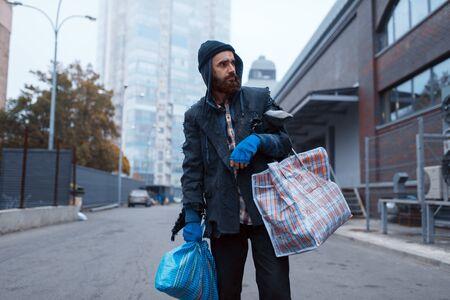Bearded tramp man with bag on city street Banco de Imagens