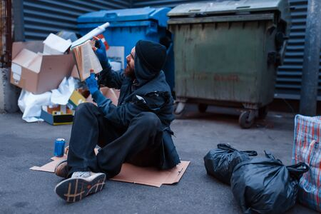 Dirty drunk beggar lies in garbage at the trashcan on city street. Poverty is a social problem, homelessness and loneliness, alcoholism and drunk addiction, urban lonely Banco de Imagens