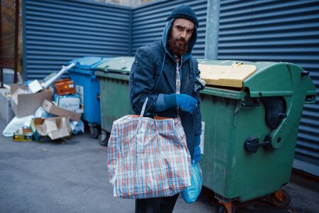 Male bearded beggar searching food in trashcan 版權商用圖片