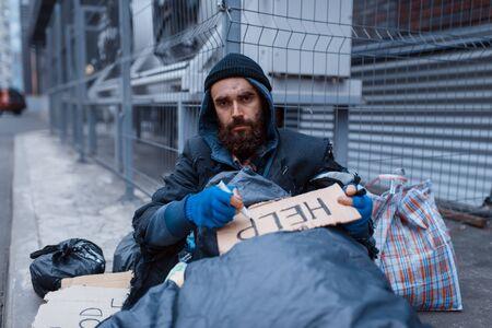 Bearded dirty homeless writes help sign