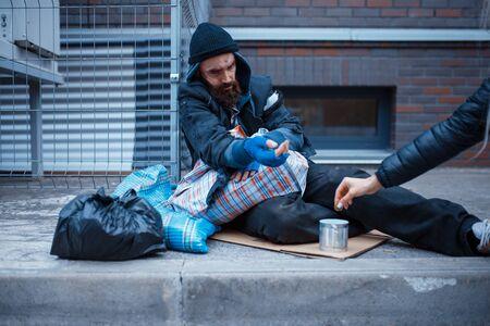Male bearded beggar begging on city street Banco de Imagens