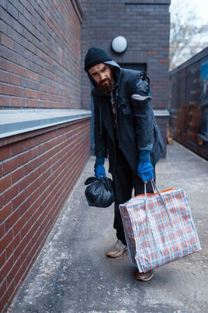Homeless man with bag on city street