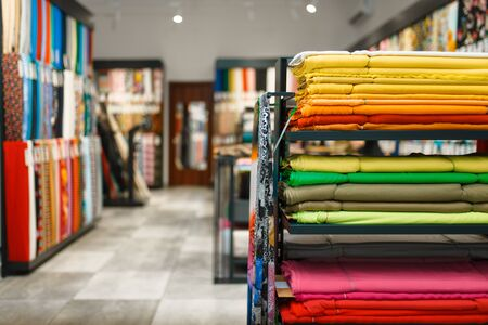 Fabric on shelves in textile store, nobody. Showcase with cloth for sewing, clothing patterns choice in shop Stock Photo