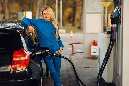 Woman fueling car on gas station, fuel refill Reklamní fotografie