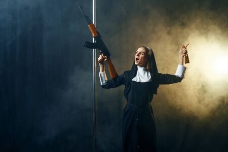 Young nun in a cassock holds assault rifle