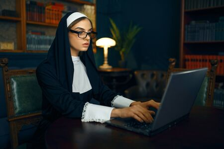 Young nun in a cassock and glasses works on laptop
