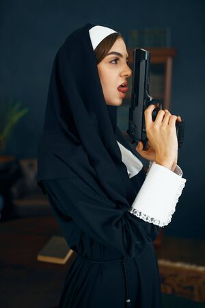 Nun in a cassock holds a gun, vicious desires Standard-Bild