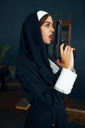Nun in a cassock holds a gun, vicious desires