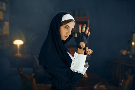 Young nun in a cassock puts on a glove