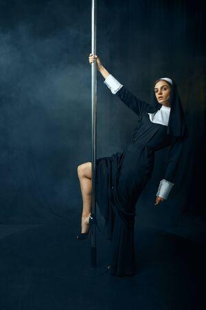 Sexy nun in cassock dances on pole like a stripper 스톡 콘텐츠