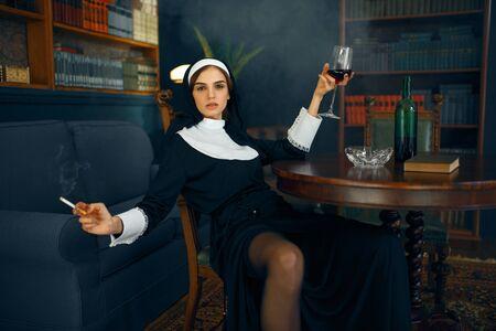 Monja sexy con cigarrillo y copa de vino