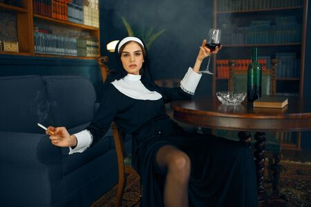 Sexy nun with cigarete and glass of wine