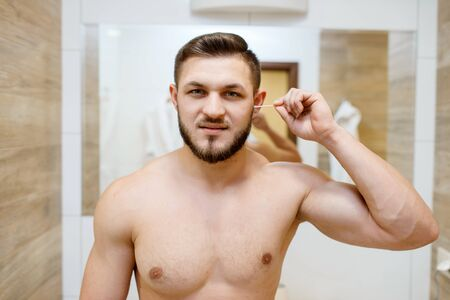 Man cleans his ears with cotton swabs in bathroom
