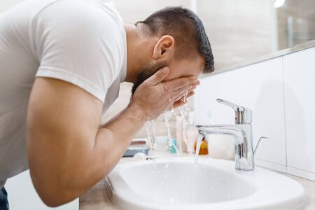 Man washes his face in bathroom, routine morning hygiene. Male person at the sink performs skin and body treatment procedures Stock Photo