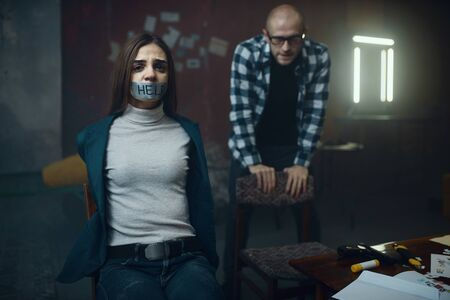 Maniac kidnapper and his victim with taped mouth