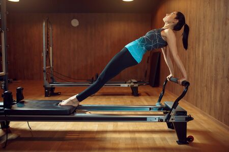 Fit woman, pilates training on exercise machine